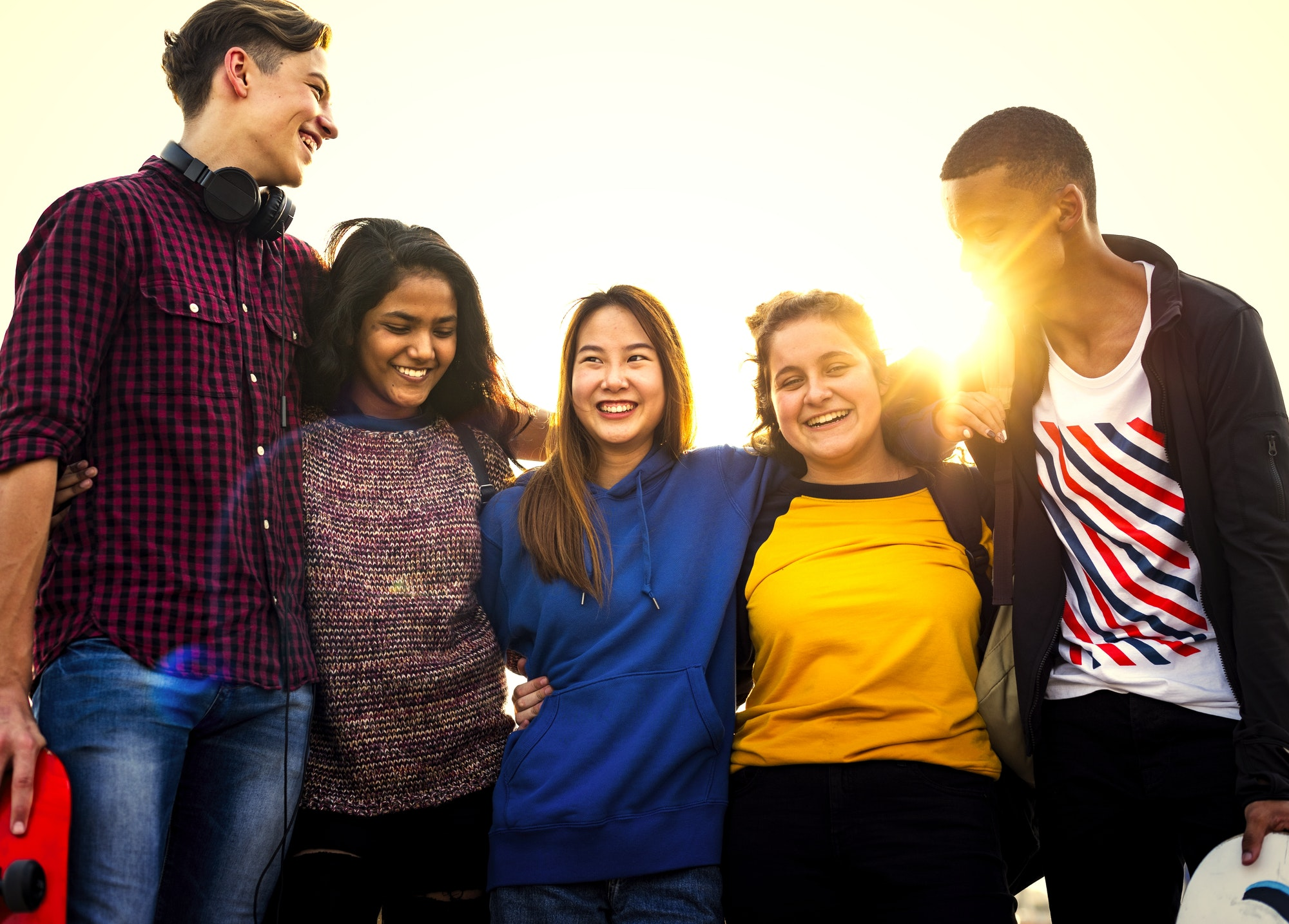 Group of school friends outdoors arms around one another togethe