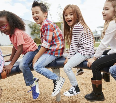 Kids playing on a spinning carousel in their schoolyard