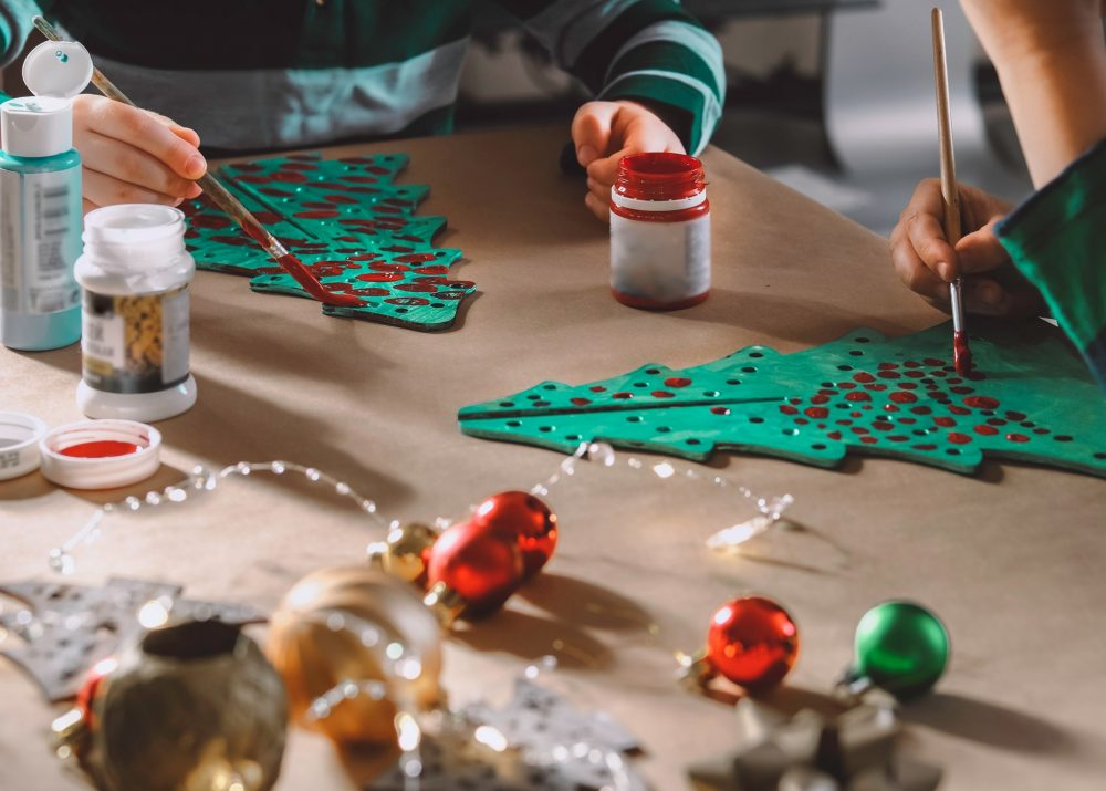 Two little kids painting wooden Christmas trees preparing holiday DIY decorations.